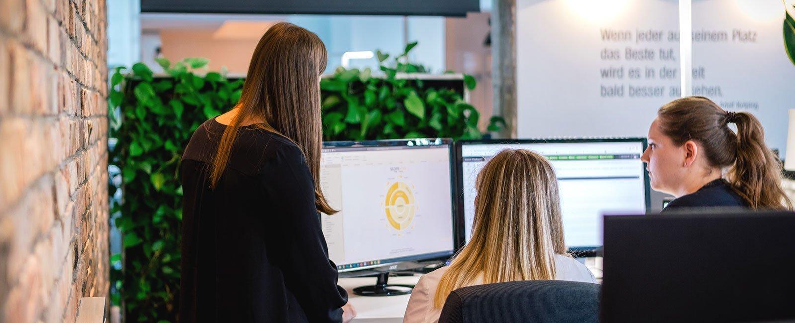 Mitarbeiterinnen gemeinsam vor einem Bildschirm mit Daten