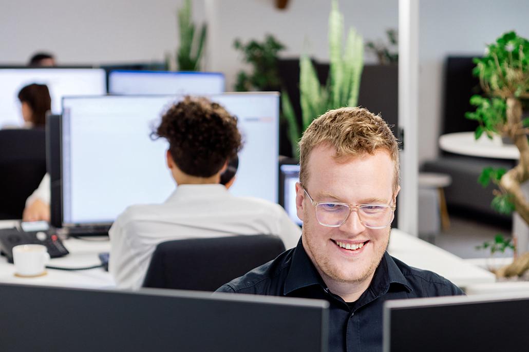 Mann sitzt am Computer und lächelt