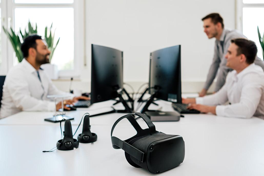 Zwei Männer sitzen im Hintergrund an ihren Computern. Im Vordergrund sieht man eine VR-Brille