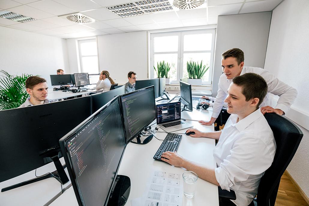 Menschen sitzen an ihrem Arbeitsplatz und schauen in den Computer