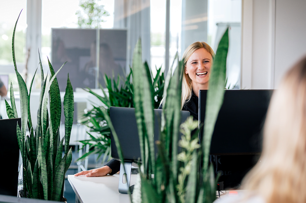 Pflanzen im Vordergrund - Mitarbeiterin lacht im Hintergrund