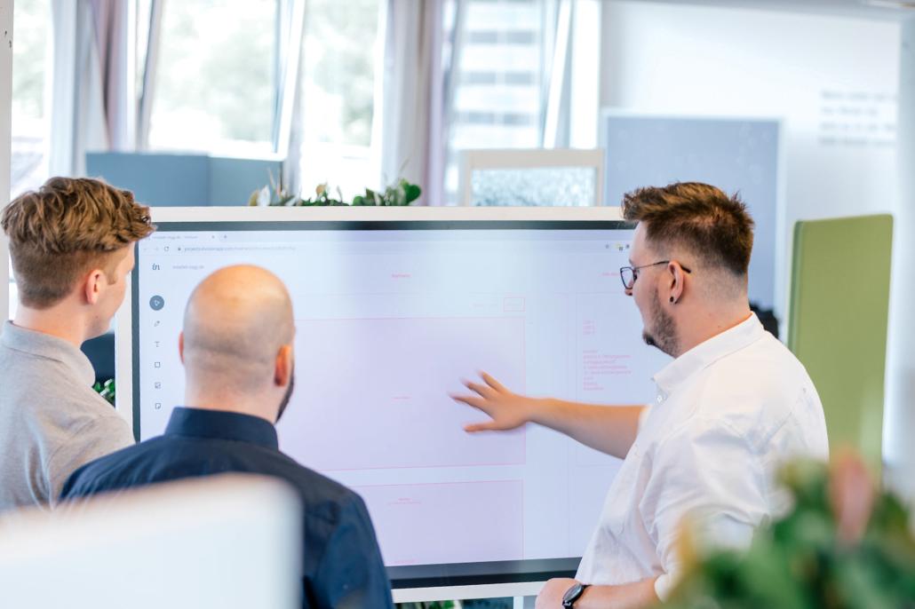 Drei Mitarbeiter stehen um ein Whiteboard herum und einer erklärt etwas