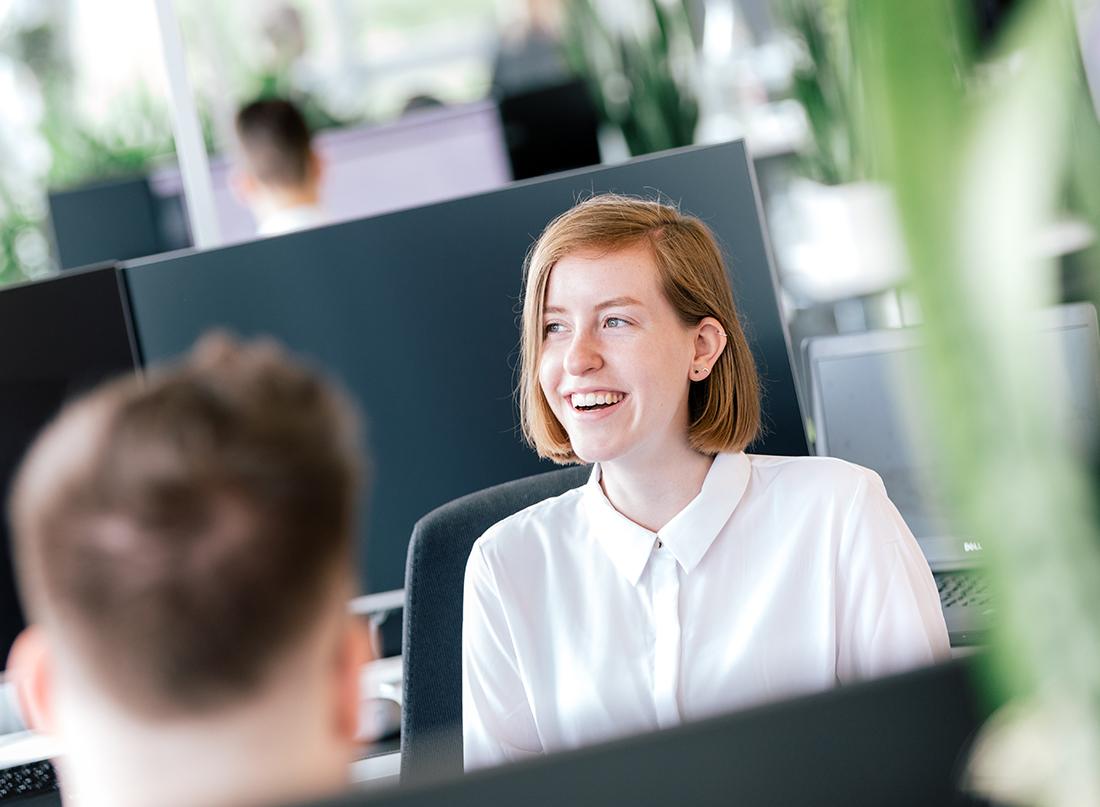 Lächelnde Mitarbeiterin sitzt am Arbeitsplatz